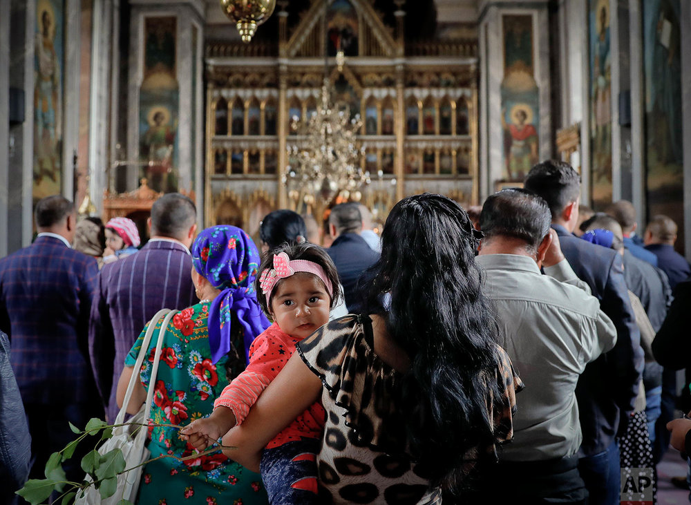 In this Friday, Sept. 8, 2017, photograph, a Roma girl is held by her mother as she attends prayers at the Bistrita monastery in Costesti, Romania. (AP Photo/Vadim Ghirda)