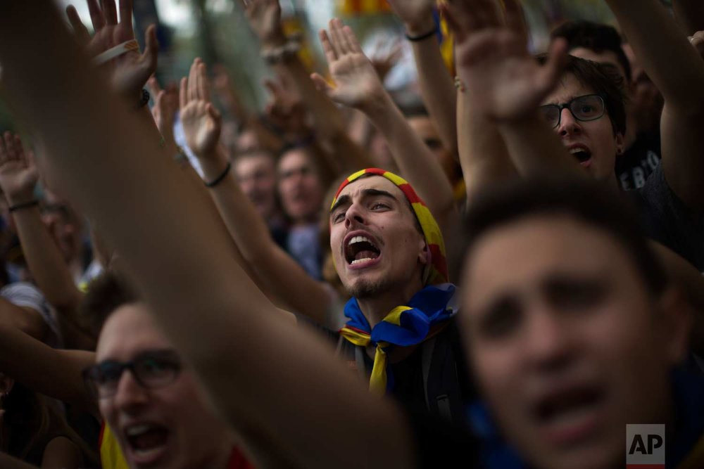 In this photo taken on Thursday, Sept. 21, 2017, people gesture and shout slogans during a protest in Barcelona, Spain. (AP Photo/Emilio Morenatti)