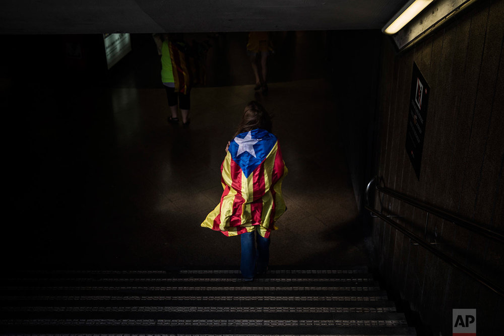"A woman enters in a Barcelona's metro station wrapped with an ""estelada"" or independence flag, during the Catalan National Day in Barcelona, Spain, on Monday, Sept. 11, 2017. Hundreds of thousands are expected to rally in Barcelona to show support for an independent Catalan nation and the right to vote in a controversial referendum that has been banned by Spain. (AP Photo/Santi Palacios)"