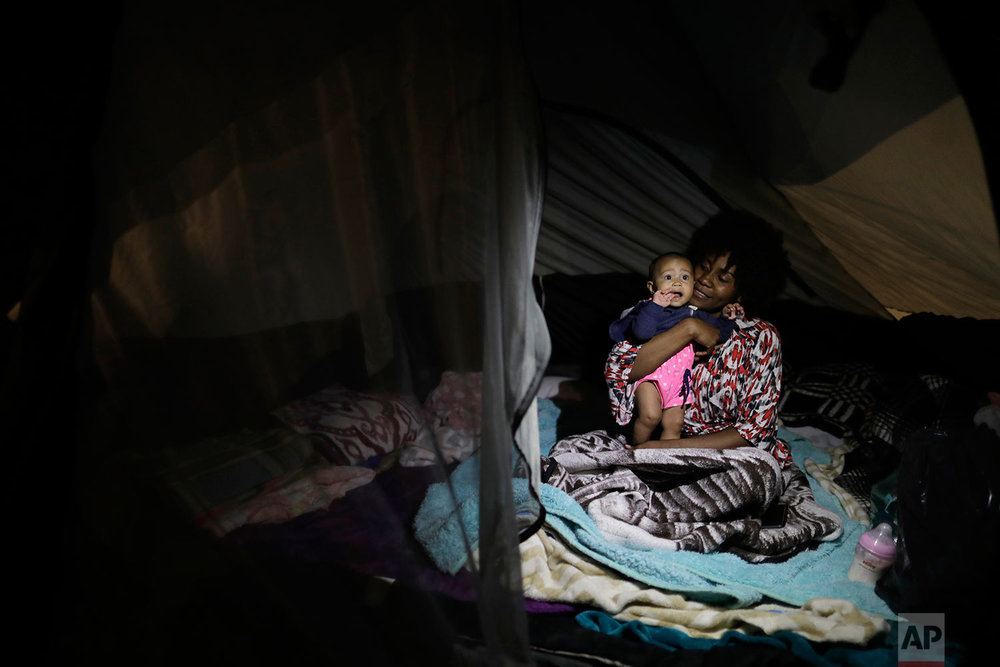Ana Jimena Jaramillo hugs her baby Xarine in their tent at the Francisco Kino school which was turned into a temporary shelter for residents evacuated from the large apartment complex in the Tlalpan neighborhood of Mexico City, Monday, Sept. 25, 2017.  (AP Photo/Natacha Pisarenko)
