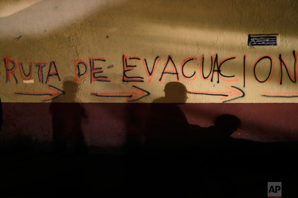 "Shadows of rescue workers and volunteers are cast on the wall of an apartment building covered with the spray painted words in Spanish: ""Evacuation route"" in the southern neighborhood of Tlalpan in Mexico City, Monday, Sept. 25, 2017. (AP Photo/Natacha Pisarenko)"