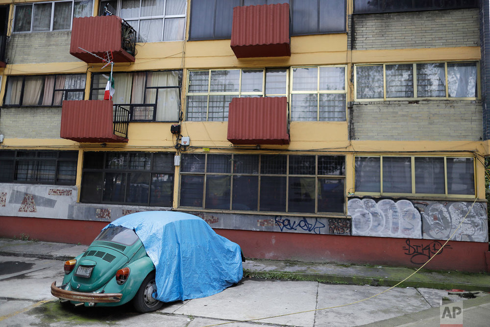 A car sits next to an evacuated apartment building at a large housing complex in the southern neighborhood of Tlalpan, Mexico City, Monday, Sept. 25, 2017. (AP Photo/Natacha Pisarenko)