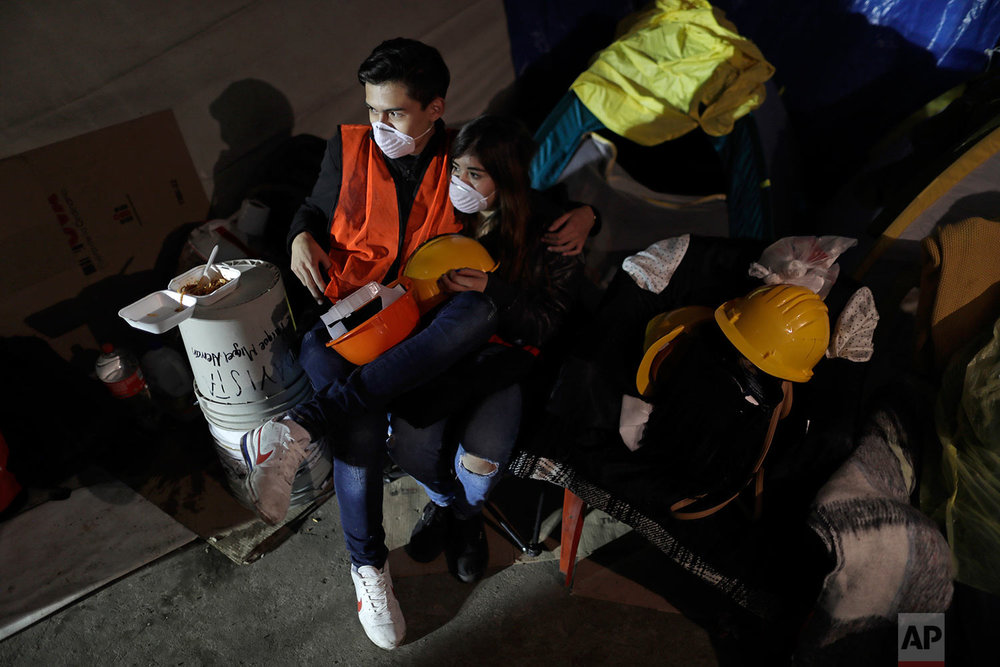 Lender Lopez, who had to evacuate his apartment, and his girlfriend Shaolin Duran prepare to spend the night at the Francisco Kino school, which was turned into a temporary shelter for residents evacuated from the large apartment complex in the Tlalpan neighborhood of Mexico City, Monday, Sept. 25, 2017.  (AP Photo/Natacha Pisarenko)