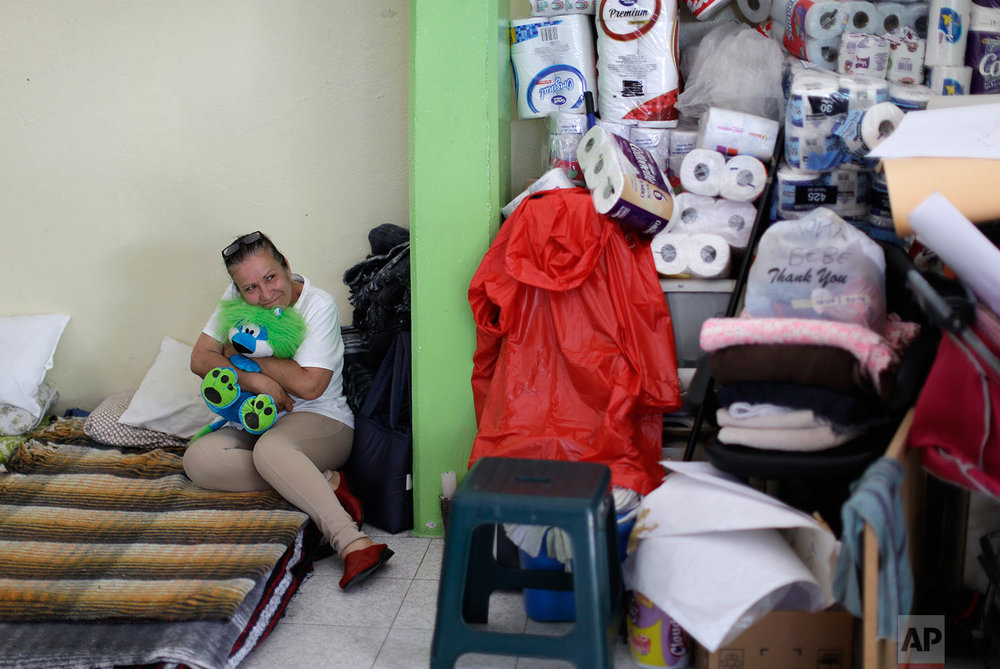 Maria Susana Fernandez hugs a teddy bear on her bed at the Francisco Kino school,  which was turned into a temporary shelter for residents evacuated from the large apartment complex in the Tlalpan neighborhood of Mexico City, Monday, Sept. 25, 2017. (AP Photo/Natacha Pisarenko)