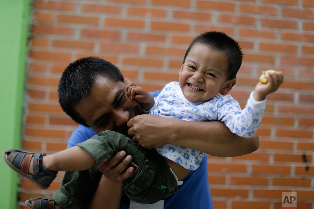 Juan Aldana plays with his son Jonatan while they live inside the Francisco Kino school, which was turned into a temporary shelter for residents evacuated from a large apartment complex in the Tlalpan neighborhood of Mexico City, Monday, Sept. 25, 2017.  (AP Photo/Natacha Pisarenko)