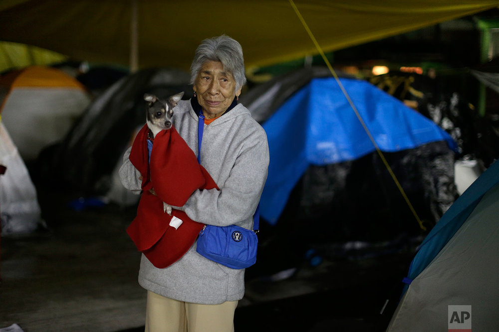 Carmen Domingues holds her puppy Coco at the Francisco Kino school, which was turned into a temporary shelter for residents evacuated from a large apartment complex in the Tlalpan neighborhood of Mexico City, Monday, Sept. 25, 2017. (AP Photo/Natacha Pisarenko)