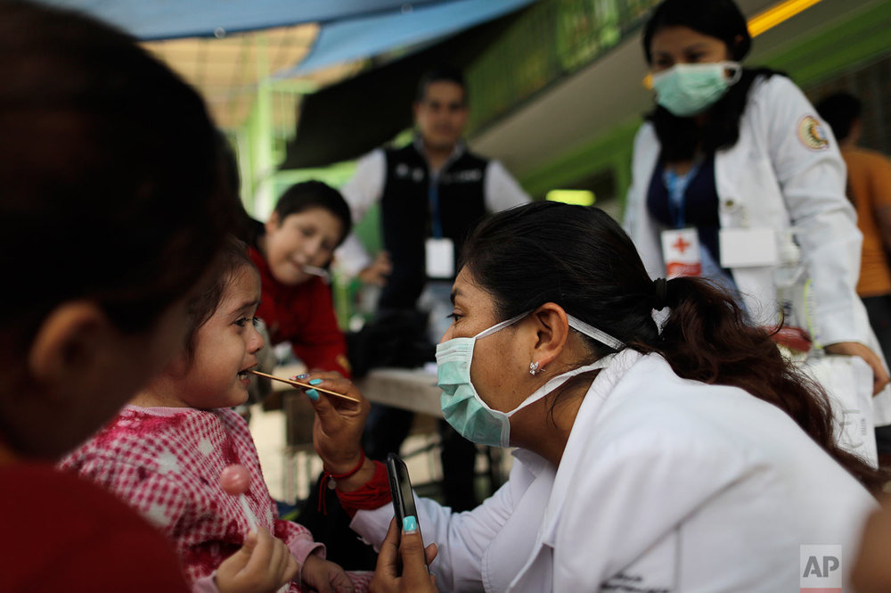 A girl is checked by a nurse at the Francisco Kino school, which was turned into a temporary shelter for residents evacuated from the large apartment complex in the Tlalpan neighborhood of Mexico City, Monday, Sept. 25, 2017.   (AP Photo/Natacha Pisarenko)