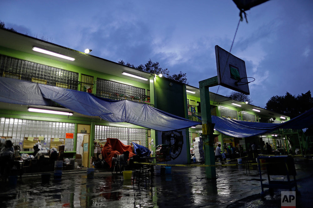 Residents displaced by the 7.1 earthquake gather in the patio of the Francisco Kino school, which was turned into a temporary shelter for residents evacuated from a large apartment complex in the Tlalpan neighborhood of Mexico City, Monday, Sept. 25, 2017.  (AP Photo/Natacha Pisarenko)