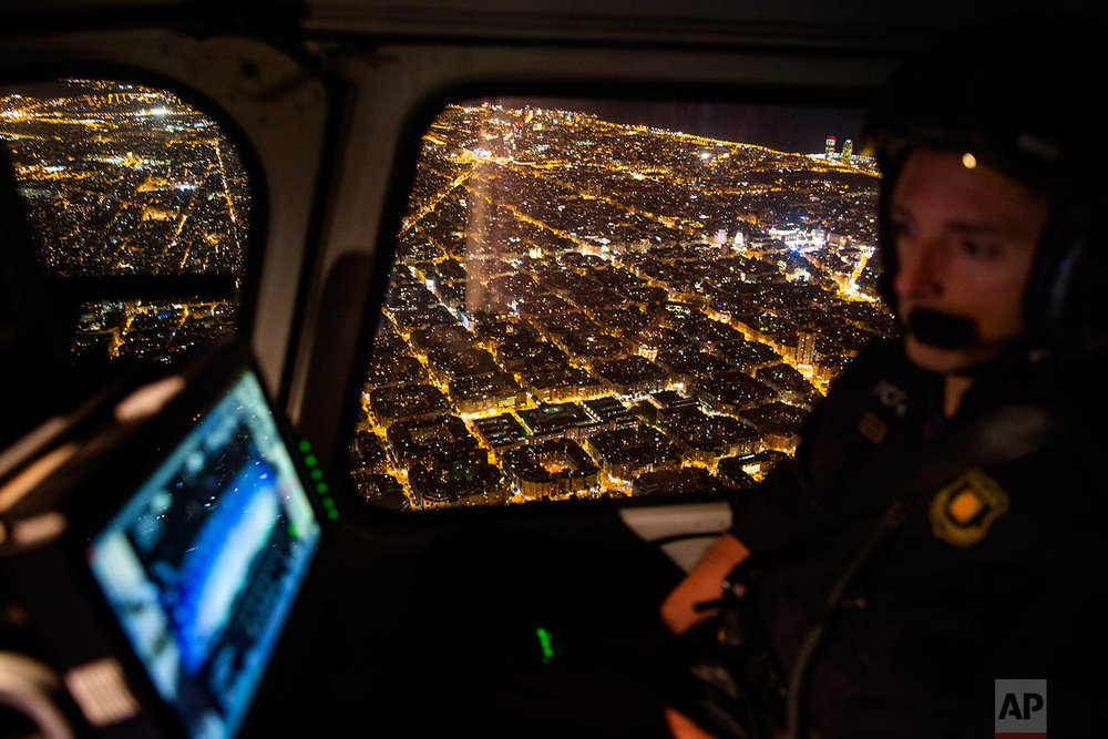 In this Tuesday, Sept. 19, 2017 photo, a Catalan Mossos d'Esquadra officer looks at the screen of a surveillance camera, as they fly over the city in a Police helicopter patrolling in Barcelona, Spain. (AP Photo/Emilio Morenatti)