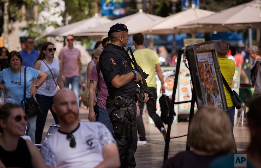 In this Saturday, Sept. 23, 2017 photo, a Catalan Mossos d'Esquadra officer holds his weapon as he patrols in la Ramblas of Barcelona, Spain.(AP Photo/Emilio Morenatti)