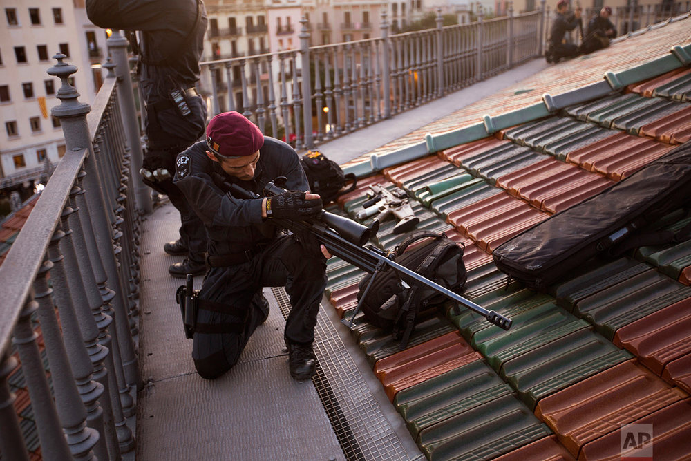 In this Sunday, Sept. 10, 2017 photo, a Catalan Mossos d'Esquadra officer from the Special forces GEI, prepares his rifle as they protect the area in the centre of Barcelona, Spain. (AP Photo/Emilio Morenatti)