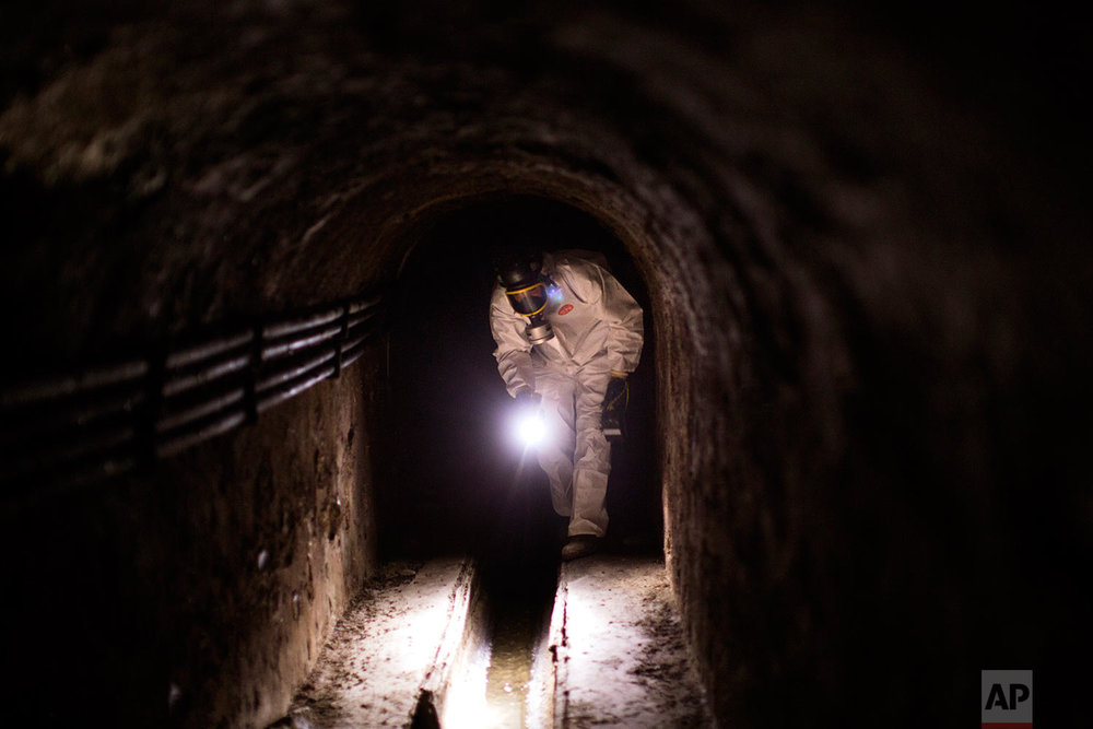 In this Sunday, Sept. 10, 2017 photo, a police officer of the Catalan Mossos d'Esquadra inspects a tunnel inside a sewer looking for possible explosives ahead of the Catalan National Day in Barcelona. (AP Photo/Emilio Morenatti)
