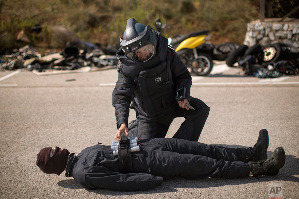 In this Tuesday, Sept. 26, 2017 photo, a Catalan Mossos d'Esquadra officer from a bomb disposal unit (TEDAX) makes a bomb disposal exercise with a mannequin during training in Sabadell, near Barcelona, Spain.  (AP Photo/Emilio Morenatti)
