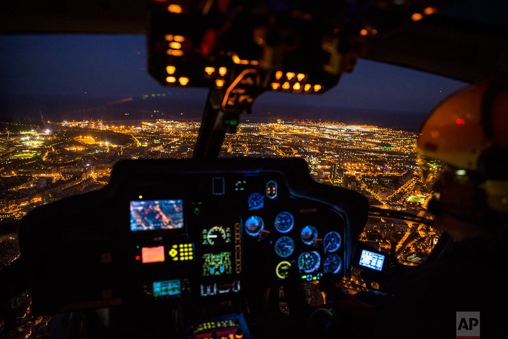 In this Tuesday, Sept. 19, 2017 photo, an officer pilots a Catalan Mossos d'Esquadra helicopter flies over the city of Barcelona, Spain during a patrol. (AP Photo/Emilio Morenatti)