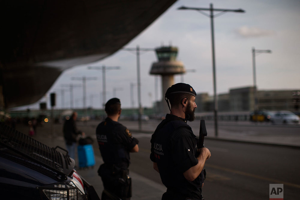 In this Thursday, Sept. 21, 2017 photo, Catalan Mossos d'Esquadra officers stand guard at one of the entrances of the Barcelona airport Barcelona airport, Spain. (AP Photo/Emilio Morenatti)