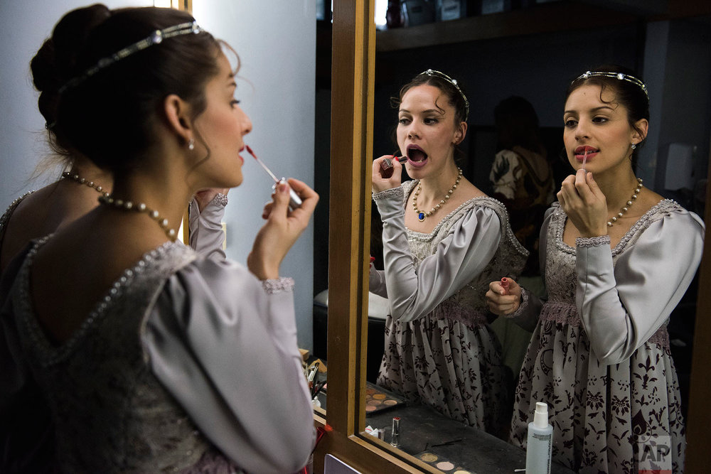 In this Friday, Sept. 15, 2017 photo, ballet dancers from Uruguay's National ballet of the Sodre put on lipstick before a dress rehearsal for Romeo and Juliet in Montevideo, Uruguay. Dancers practice Monday through Friday for eight hours at a time. (AP Photo/Matilde Campodonico)