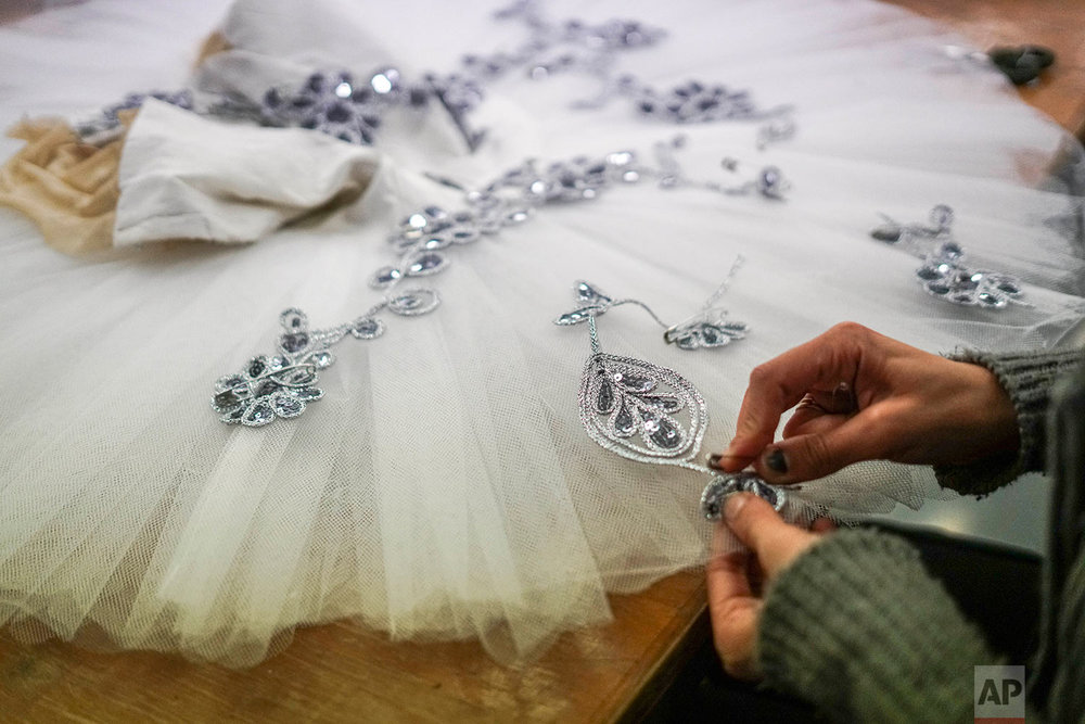 In this Friday, Sept. 15, 2017 photo, a seamstress sews a tutu for The Nutcracker production by Uruguay's National ballet of the Sodre in Montevideo, Uruguay. (AP Photo/Matilde Campodonico)