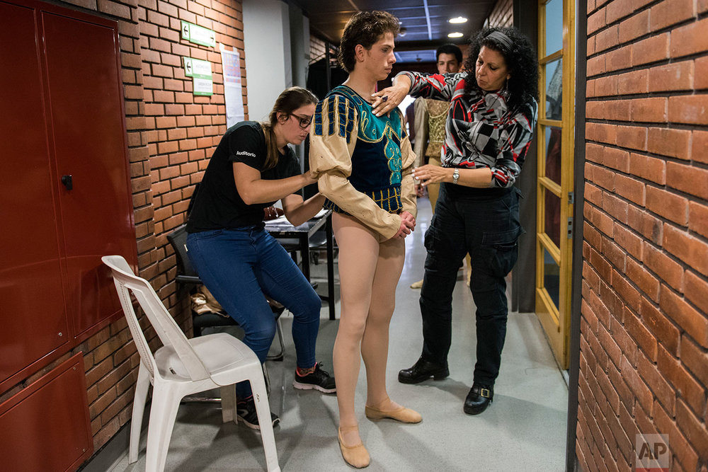 In this Tuesday, Sept. 19, 2017 photo, principal dancer Ciro Tamayo is helped by costume assistants before a dress rehearsal of Romeo and Juliet in Montevideo, Uruguay.   (AP Photo/Matilde Campodonico)