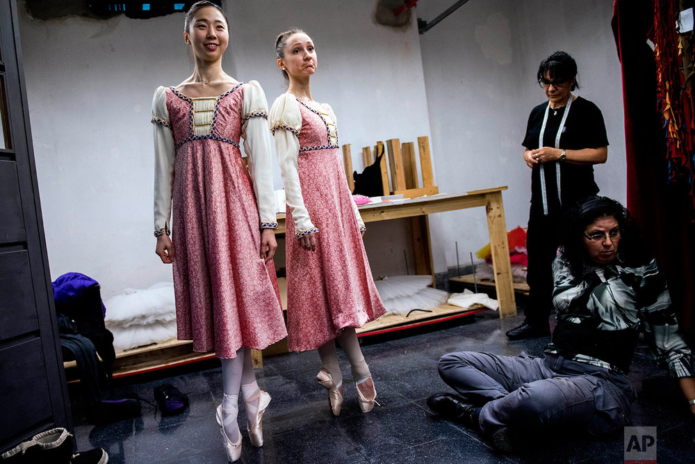 In this Wednesday, Sept. 6, 2017 photo, ballet dancers Eunsil Kim, left, and Paula Penachio try on their dresses at the costume workshop at the Adela Reta Auditorium in Montevideo, Uruguay. (AP Photo/Matilde Campodonico)