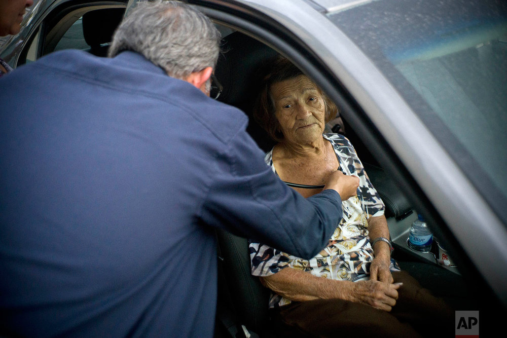 "Carmen Hernandez, who lives in a senior living facility that lacks water and electricity in the wake of Hurricane Maria, is checked on by a doctor after she fell down, as she sits still for the doctor inside a car parked outside the hospital for lack of space at the hospital, in Bayamon, Puerto Rico, Thursday, Sept. 28, 2017. Hernandez most desired for people to care for the island's senior citizens in terms of restoring utilities during such high temperatures. ""Don't forget the weakest (people), us elderly folks."" (AP Photo/Ramon Espinosa)"
