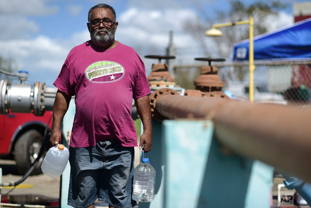 "In this Sept. 29, 2017 photo, Lebron Eduardo poses for a portrait as he makes his daily trip to a drinking water supply station in Santa Isabel, Puerto Rico. Eduardo said his greatest need at the moment is water. ""Water is not reaching the neighborhood"", said the 60-year-old Santa Isabel resident. (AP Photo/Carlos Giusti)"