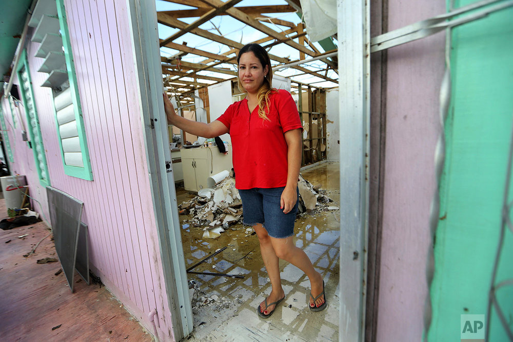 "In this Sept. 29, 2017 photo, Sandy Nieves poses for a portrait in the door of her heavily damaged home in the aftermath of Hurricane Maria in Yabucoa, Puerto Rico. Nieves said her greatest need is her home and especially her baby's bed. ""We don't have anywhere to sleep, we don't have our stuff. We are all sleeping in one bed at my mom's house."" (AP Photo/Gerald Herbert)"