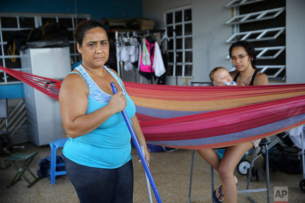 "In this Sept. 29, 2017 photo, Maria Yuseno poses for a portrait with her daughter Edmary Martinez as she sweeps out her carport containing belongings salvaged from their damaged home after the passing of Hurricane Maria in Yabucoa, Puerto Rico. They say their most urgent need is food. Edmary says; ""Food gets to the supermarkets, but they run out almost immediately. And the ships, they aren't arriving."" (AP Photo/Gerald Herbert)"