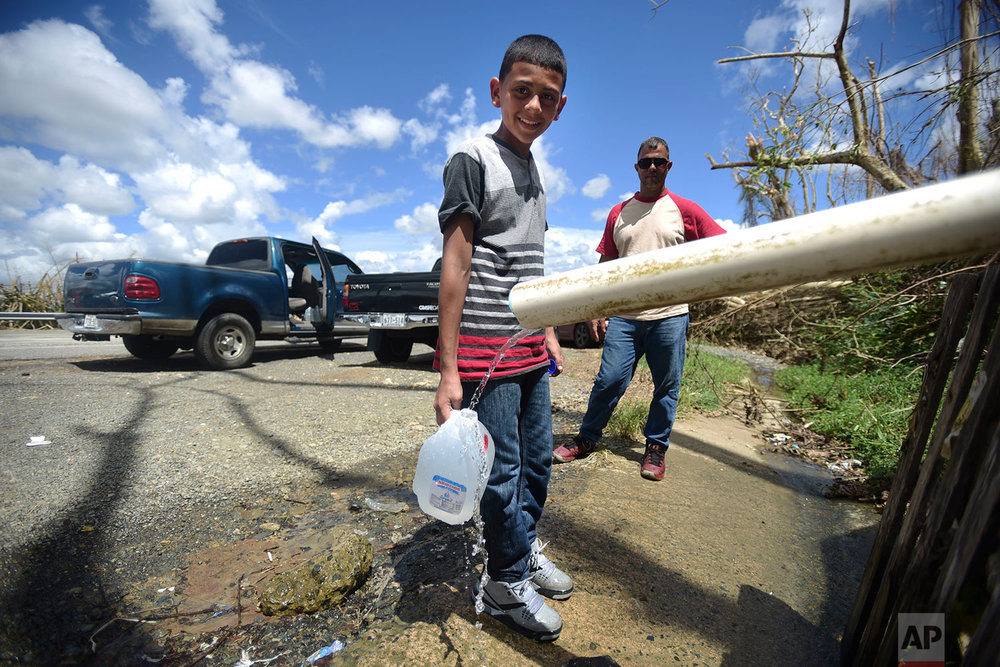 "In this Sept. 29, 2017 photo, 13-year-old Dereck Laguna accompanies his stepfather Jose Figueroa as they stop along the highway where they located water in Cayey, Puerto Rico. Laguna and Figueroa said their greatest need is water. ""Right now we don't even have a little bottle of water in the house. At least I move around, I have my car and I look for water to drink. It's hard to do but you have to move around,"" Figueroa said. (AP Photo/Carlos Giusti)"