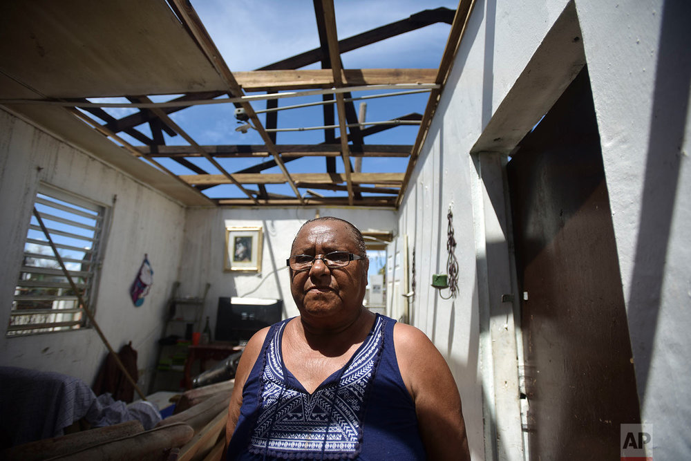 "In this Sept. 29, 2017 photo, Sonia Rodriguez stands in her home damaged by the passage of Hurricane Maria in Salinas, Puerto Rico. Rodriguez said her greatest need is to replace her home's roof. ""It's too hard. This is the house my parents left me. They already died. To lose it like that after so much effort to maintain it ... at least I'm alive"", Rodriguez said while trying to hold back tears. (AP Photo/Carlos Giusti)"