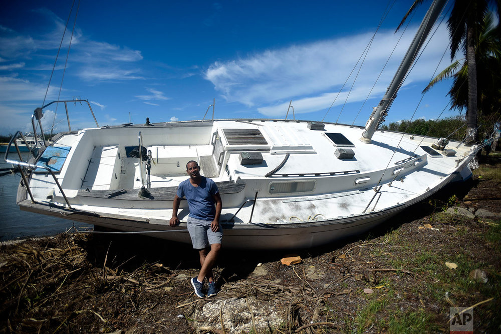 "This Sept. 29, 2017 photo shows Rafael Velazquez, a resident of Cayey, posing for a portrait next to his boat lying on the bank after the storm surge brought by Hurricane Maria in Santa Isabel, Puerto Rico. Velazquez, who is applying to study his doctorate in chemical physics at the University of Puerto Rico, said his greatest need is to put the boat back in the water. ""I bought it a year ago and hadn't used it yet. The storm premiered it for me,"" said Velazquez. (AP Photo/Carlos Giusti)"