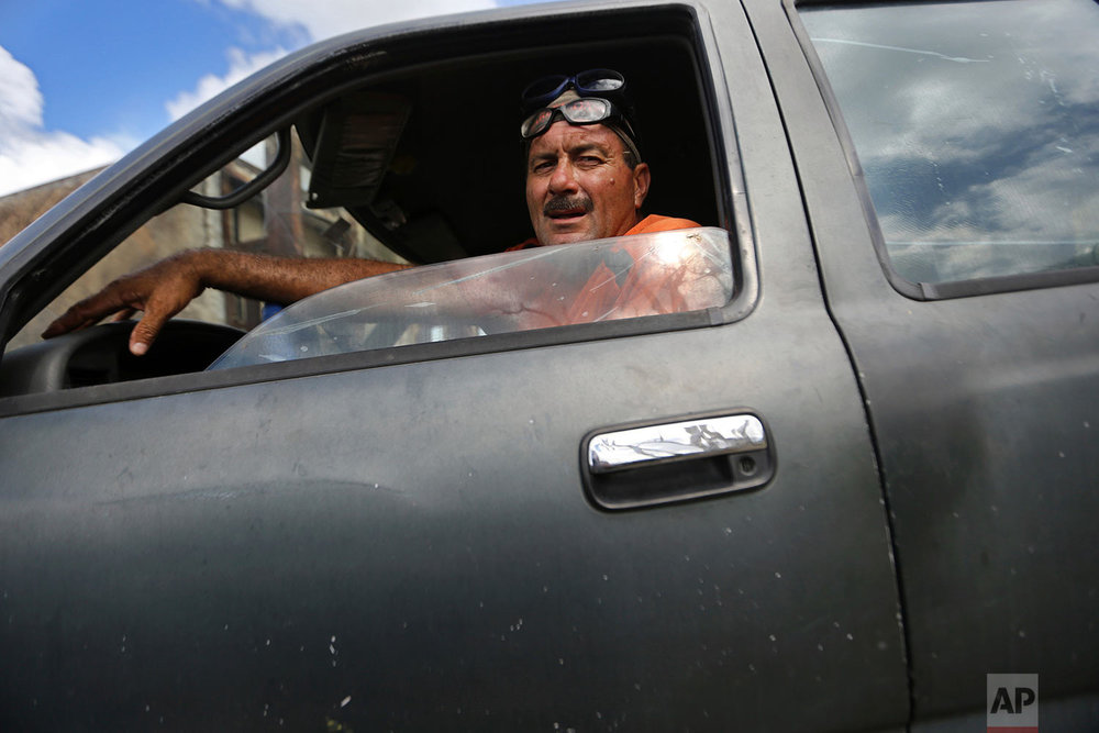 "In this Sept. 29, 2017 photo, Cesar Lopategui poses for a portrait after hauling storm debris to the municipal dump, in the aftermath of Hurricane Maria in Yabucoa, Puerto Rico. Lopategui said he feels the most important need is for people to unite. ""We can get through this whole thing instead of everybody pushing for themselves."" (AP Photo/Gerald Herbert)"