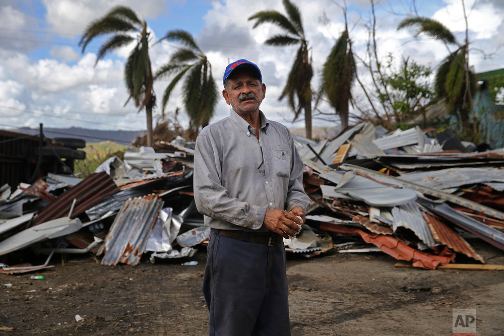 "In this Sept. 29, 2017 photo, Felix Davilla, who works at the Yabucoa dump, poses for a portrait in front of debris dropped off by residents in the aftermath of Hurricane Maria in Yabucoa, Puerto Rico. ""The most necessary is water and canned food. Also we have no electricity. And medicine. These (water, electricity, medicine) are our primary needs."" (AP Photo/Gerald Herbert)"