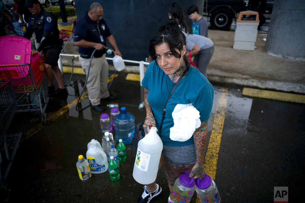 "Emari Rodriguez poses for a portrait after filling up bottles at a water distribution center to take it home, which is intact, but lacks water and electricity, in the wake of Hurricane Maria in Bayamon, Puerto Rico, Thursday, Sept. 28, 2017. Rodriguez, who lacks water and electricity at home, but which is still in tact, said she's most worried about the elderly in her neighborhood. ""We need the electricity to return, since the elderly won't hold up much more with this situation. We need to move forward.""  (AP Photo/Ramon Espinosa)"