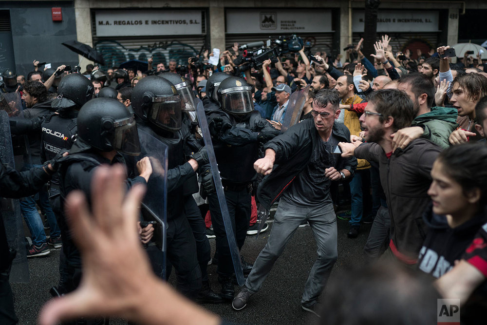 People confronts Spanish riot police near a voting site at a school assigned to be a polling station by the Catalan government in Barcelona, Spain, Sunday, 1 Oct. 2017. Spanish riot police have forcefully removed a few hundred would-be voters from several polling stations in Barcelona.(AP Photo/Felipe Dana)