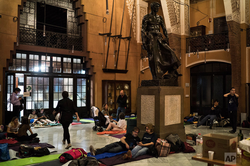 People prepare to spend the night inside a school listed to be a polling station by the Catalan government in Barcelona, Spain, Saturday, Sept. 30 2017. Catalan pro-referendum residents vowed Saturday to ignore a police ultimatum to leave the schools they are occupying to use in a vote seeking independence from Spain.(AP Photo/Felipe Dana)