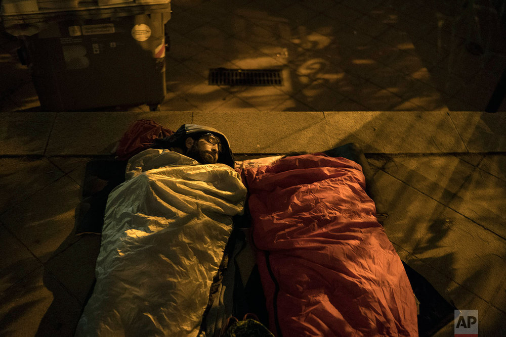 Pro-referendum supporters sleep at the yard of the Escola Industrial, a school listed to be a polling station by the Catalan government, in Barcelona, Spain, Sunday, Oct. 1, 2017. Catalan pro-referendum supporters vowed to ignore a police ultimatum to leave the schools they are occupying to use in a vote seeking independence from Spain.(AP Photo/Felipe Dana)