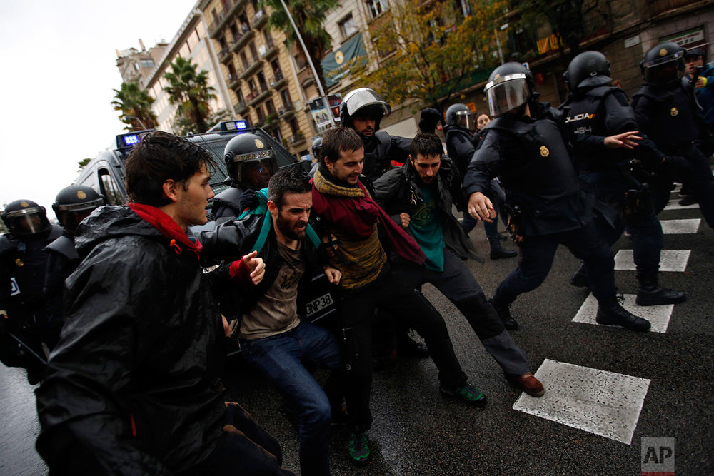 Spanish National Police push away Pro-referendum supporters outside the Ramon Llull school assigned to be a polling station by the Catalan government in Barcelona, Spain, early Sunday, Oct. 1, 2017. Catalan pro-referendum supporters vowed to ignore a police ultimatum to leave the schools they are occupying to use in a vote seeking independence from Spain. (AP Photo/Emilio Morenatti)