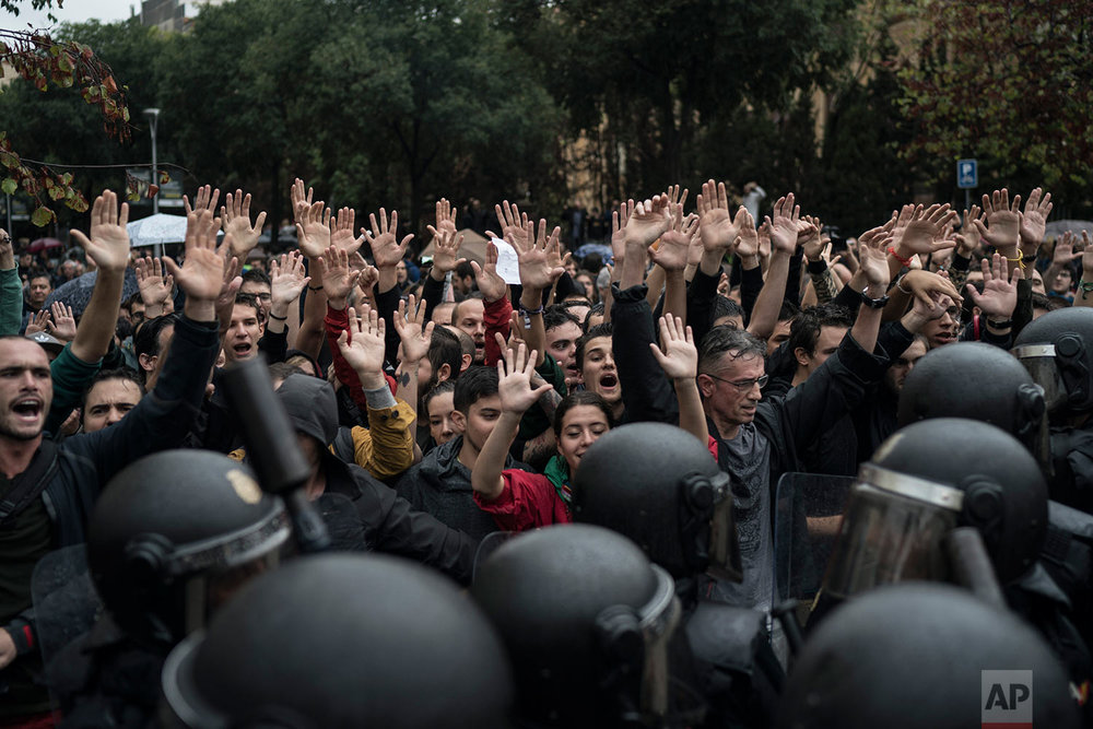People confronts Spanish riot police near a voting site at a school assigned to be a polling station by the Catalan government in Barcelona, Spain, Sunday, 1 Oct. 2017. Spanish riot police have forcefully removed and clashed with would-be voters in several polling stations in Barcelona.(AP Photo/Felipe Dana)