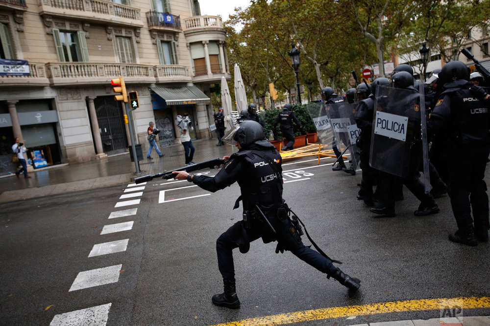 Spanish riot police shoots rubber bullet straight to people trying to reach a voting site at a school assigned to be a polling station by the Catalan government in Barcelona, Spain, Sunday, Oct. 1, 2017. Spanish riot police have forcefully removed a few hundred would-be voters from several polling stations in Barcelona. (AP Photo/Emilio Morenatti)