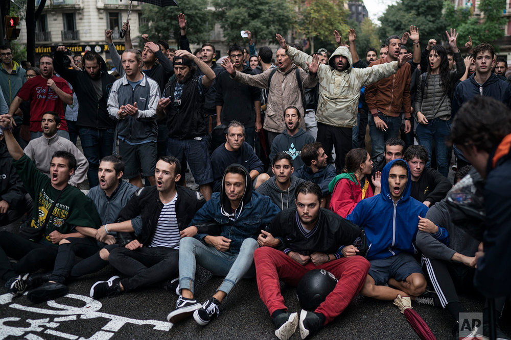 People sits in the middle of the street to block Spanish riot police near a voting site at a school assigned to be a polling station by the Catalan government in Barcelona, Spain, Sunday, 1 Oct. 2017. Catalan pro-referendum supporters vowed Saturday to ignore a police ultimatum to leave the schools they are occupying to use in a vote seeking independence from Spain. (AP Photo/Felipe Dana)