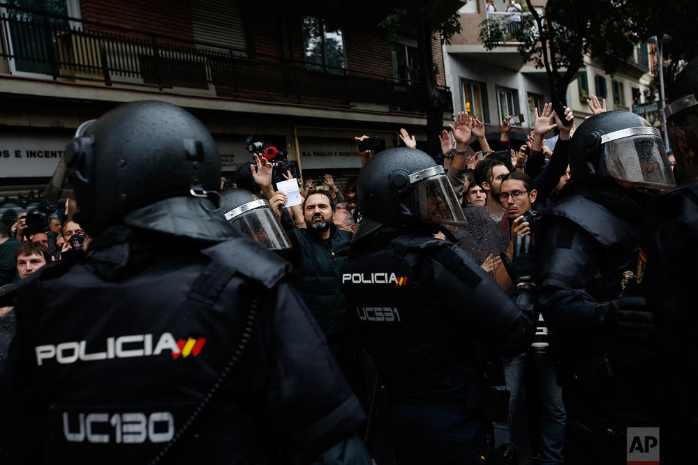 A man shows a ballot paper as Spanish National Police blocks people from approaching the Ramon Llull school assigned to be a polling station by the Catalan government in Barcelona, Spain, early Sunday, 1 Oct. 2017. Catalan pro-referendum supporters vowed to ignore a police ultimatum to leave the schools they are occupying to use in a vote seeking independence from Spain. (AP Photo/Emilio Morenatti)