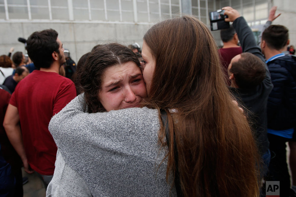 A woman cries after civil guards dragged people away from the entrance of a sports center, assigned to be a referendum polling station by the Catalan government in Sant Julia de Ramis, near Girona, Spain, Sunday, Oct. 1, 2017. Scuffles have erupted as voters protested as dozens of anti-rioting police broke into a polling station where the regional leader was expected to show up for voting on Sunday. (AP Photo/Francisco Seco)