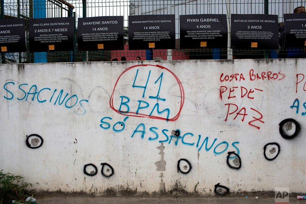 This April 12, 2017 photo shows an outer wall of the Daniel Piza Municipal School riddled with bullets, alongside spray painted messages labeling Battalion 41 of the military police as assassins, at the Acari slum, in Rio de Janeiro, Brazil. The toll the violence takes on children attracted national attention on March 30 when a 13-year-old girl was shot and killed at the school, when she was caught in the crossfire of a lengthy shootout between police and gangsters. (AP Photo/Silvia Izquierdo)