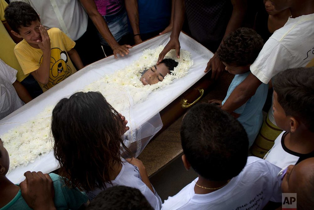In this April 26, 2017 photo, friends and relatives surround the coffin containing the remains of 13-year-old Paulo Henrique Oliveira, during a burial ceremony in Rio de Janeiro, Brazil. With an estimated average of 15 shootings per day involving police and heavily armed gangs that control large swaths of the city, hundreds of civilians have been killed or injured in the crossfire, and increasingly that includes children, scores of who like Oliveira have been felled by bullets intended for others. (AP Photo/Silvia Izquierdo)