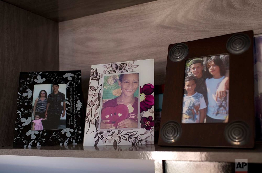 In this Aug. 13, 2017 photo, family portraits of Felipe Farias line a shelf in his mother's new apartment, in the Alemao complex of slums, in Rio de Janeiro, Brazil. The 16-year-old was killed on April 26 in the Alemao while returning from a protest condemning the death of a 13-year-old who was also killed by gunfire. (AP Photo/Silvia Izquierdo)