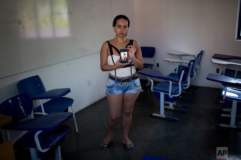 In this Sept. 6, 2017 photo Thayana Caparica poses with a photo of her 7-year-old daughter Fernanda, at the Mare complex of slums, in Rio de Janeiro, Brazil. Classes at Fernanda's school were canceled on the morning of Feb. 15, due to gunfire between gangs. Caparica took her daughter home and ordered Fernanda and her two brothers not to leave the house. But by the afternoon Fernanda had grown impatient and wanted to play outside. She kept insisting. Finally Caparica let her go to a friend's house. Later that day she learned that her daughter had been shot in the face. (AP Photo/Silvia Izquierdo)