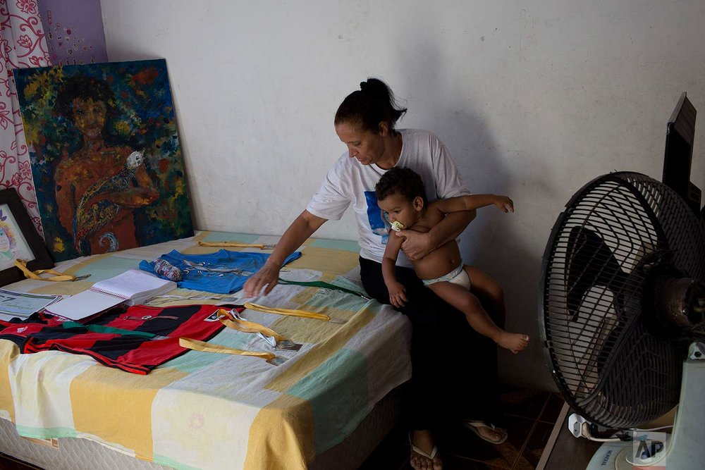 "In this July 26, 2017 photo, Rosilene Alves Ferreira, mother of Maria Eduarda Alves da Conceicao, cradles Lucas, a baby she hopes to adopt, as she reflects on her slain daughter's belongings, at her home in the Acari slum, Rio de Janeiro, Brazil. Her daughter was hit by several rounds at the school entrance as she walked to the water fountain.""They saw it was a school, and they kept shooting,"" said Ferreira. ""Over 60 shots were fired."" (AP Photo/Silvia Izquierdo)"