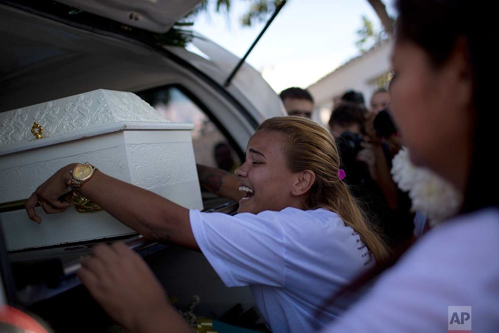 In this July 6, 2017 photo, Laisa accompanies the coffin containing the remains of her friend and neighbor, 10-year-old Vanessa dos Santos, as the remains are transported to the burial site, at a cemetery in Rio de Janeiro, Brazil. On July 4, a group of police officers on patrol barged into Vanessa's home. As she turned to flee shooting erupted. She died on the doorstep with a high caliber bullet wound to the head. (AP Photo/Silvia Izquierdo)