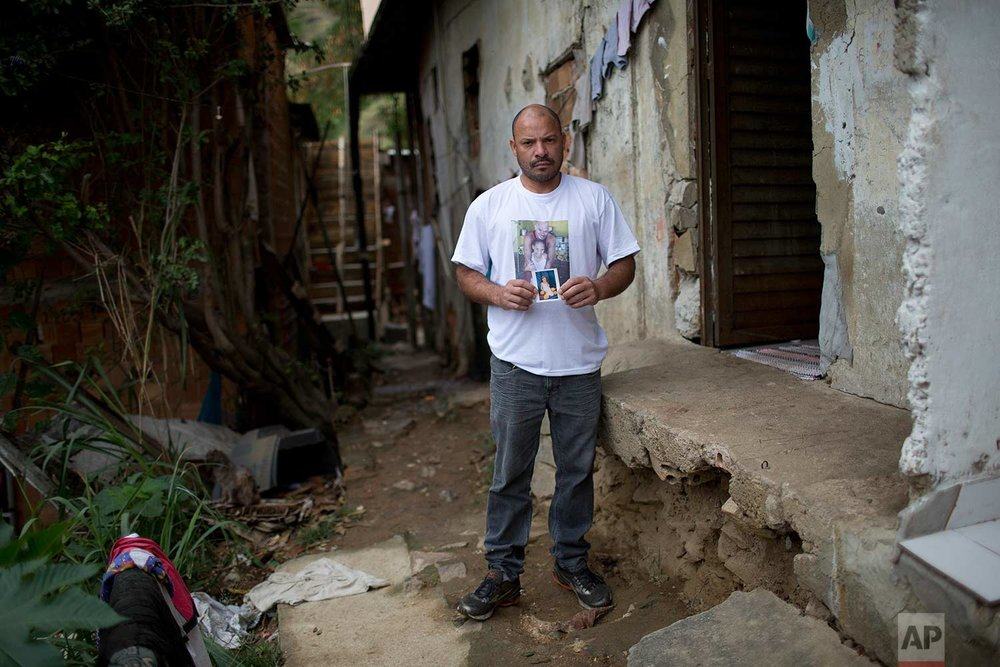 "In this Aug. 23, 2017 photo, Leandro Monteiro de Matos poses with a photo of his 10-year-old daughter Vanessa Dos Santos, standing in the exact place where his daughter fell dead from a high caliber bullet wound to the head not meant for her, in the Lins complex of slums, Rio de Janeiro, Brazil. ""I used to imagine the bad things that could happen, like a car running over my child,"" said Matos, who had already moved out of the slum years ago after divorcing Vanessa's mother. ""But now I'm neurotic. Everything scares me."" (AP Photo/Silvia Izquierdo)"