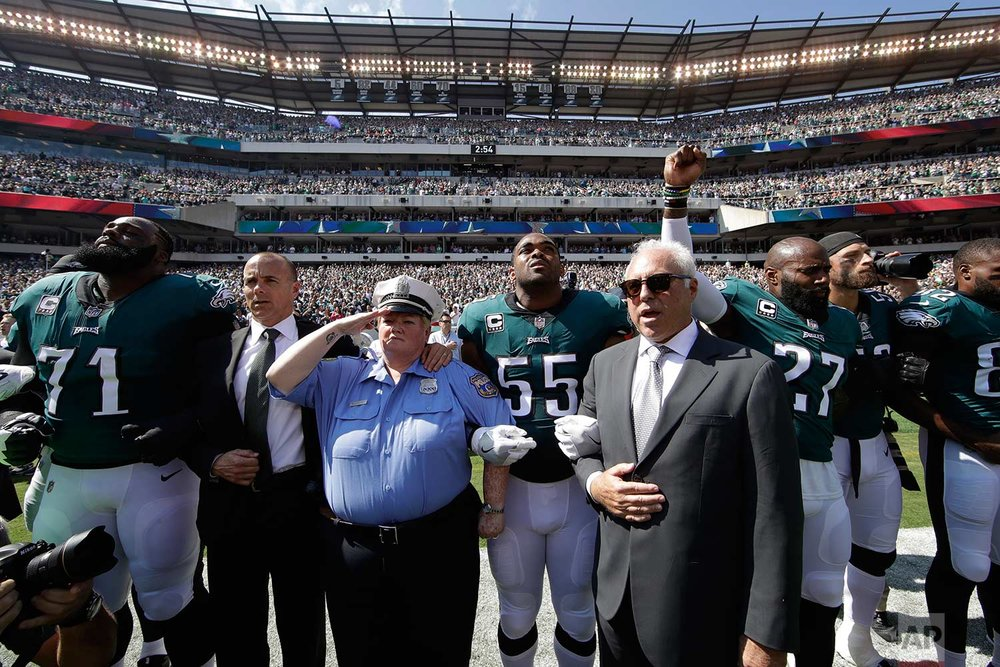 Philadelphia Eagles players, owner Jeffrey Lurie, center right, Eagles' President Don Smolenski, second from left, and a Philadelphia police officer, third from left, stand for the national anthem before an NFL football game against the New York Giants, Sunday, Sept. 24, 2017, in Philadelphia. Eagles' Malcolm Jenkins raises his fist next to Lurie. (AP Photo/Matt Rourke)